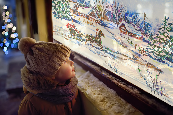 Child looking at a store window with a winter-themed painting on it.